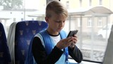 Boy going to school by tram sit and type his smartphone chatting in transport by the window - 221143108