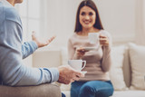 Informal atmosphere. Selective focus of a cup of coffee in hands of a professional male psychologist while talking to his client - 221143396