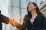 business asian woman in modern black suit handshake with people after finishing up meeting in city, partnership, teamwork, community, connection financial and investment concept - 221145739