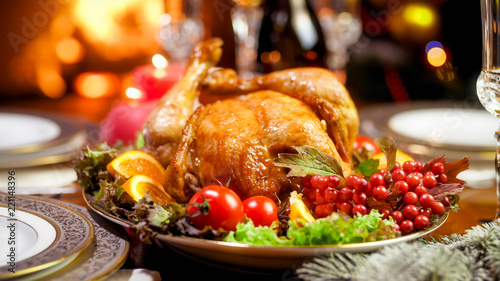 Leinwandbild Motiv Closeup image of tasty baked chicken on festive table served at living room with fireplace