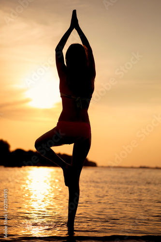 Poster Silhouette woman yoga on the beach at sunset.