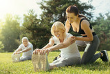 You are doing well. Cheerful trainer and positive minded elderly woman beaming while doing a stretching exercise outdoors. - 221157501
