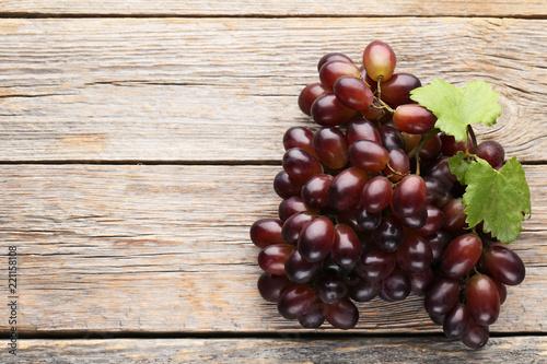 Leinwanddruck Bild Red grape on grey wooden table