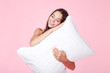 Young girl with white pillow on pink background