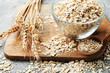 Leinwanddruck Bild - Oatmeal in bowl on brown cutting board