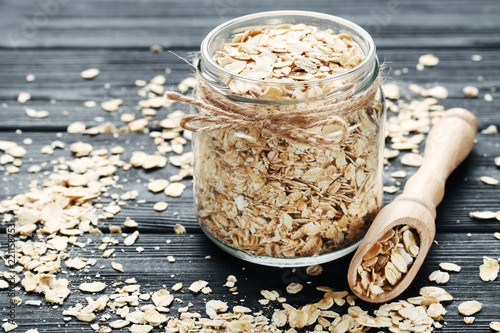 Oatmeal in glass jar on black wooden table - 221158753