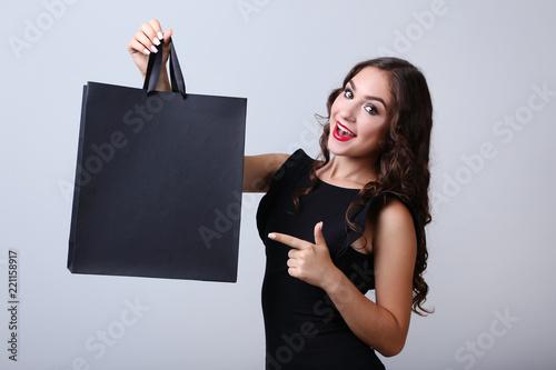 Leinwandbild Motiv Happy woman with shopping bag on grey background