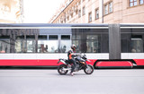 Motorcyclist on a motorcycle is standing on the road with a modern tram. Public transport and a stylish motorcyclist in a helmet. Street photo.