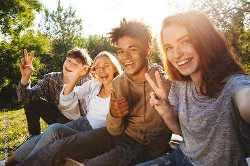 Leinwandbild Motiv Group of excited multhiethnic students doing homework