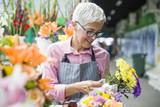 Senior woman sales flowers on local flower market - 221161909