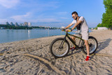 a young guy on a bicycle with big wheels is riding on the river bank in the sand against the backdrop of a big city on a clear hot summer day