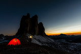 Night bivouac at Tre Cime di Lavaredo, milion star hotel under night sky, red iluminated tent on pass in Dolomites, Italy. - 221173307