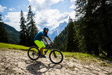 Tourist cycling in Cortina d'Ampezzo, stunning rocky mountains on the background. Man riding MTB enduro flow trail. South Tyrol province of Italy, Dolomites. - 221173931