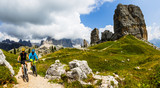 Tourist cycling in Cortina d'Ampezzo, stunning Cinque Torri and Tofana in background. Woman and man riding MTB trail. South Tyrol province of Italy, Dolomites. - 221174550