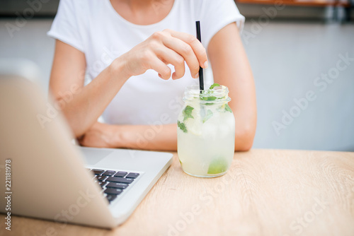 Naklejka Woman with lemonade and laptop in cafe. Copy space.