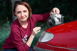 a young girl stands at a broken car and holds a bad spare part, an electric generator, does not understand how to repair, clean it with a cloth - 221188739