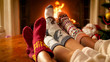 Leinwanddruck Bild - Family wearing warm knitted socks relaxing at house with burning fireplace