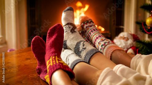 Leinwanddruck Bild Family wearing warm knitted socks relaxing at house with burning fireplace