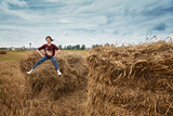 young girl having fun in the field, sitting on a haystack - 221189129
