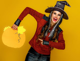 happy woman isolated on yellow background pointing at pumpkin - 221193577