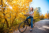 Active woman riding bicycle at autumn day - 221200383