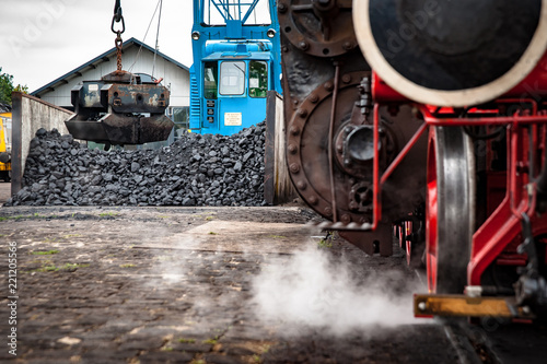 Steaming steam train or locomotive is waiting for coal loading by a vintage crane, industrial details and craftsmanship along the rail way and train station