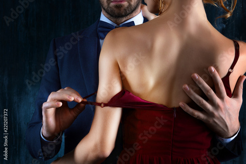 Leinwandbild Motiv Elegant couple in love. Rich tidy neat man male hugs luxury woman female in red evening dress with expensive gold earrings. Romantic dating body part, sex social issues, relationship concept