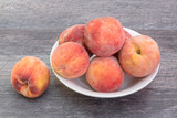 Fresh, ripe peaches in white bowl, on wooden background - 221212755