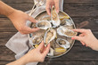 Leinwandbild Motiv Top view of people with fresh oysters at table, focus on hands