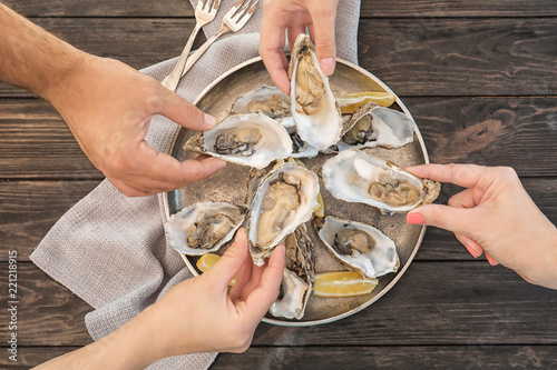 Top view of people with fresh oysters at table, focus on hands - 221218915