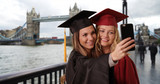 Couple of college grads taking selfie with phone for graduation in London - 221222306