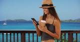Cute young woman vacationing in the Caribbean texting with smartphone - 221228160