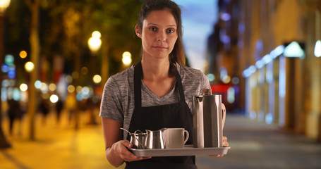 Pretty waitress on the Champs-Elysees carrying tray with coffee beverages