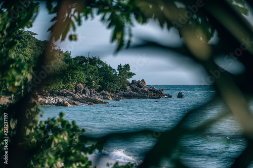 Foto Murales Beautiful beach photography. Beach seen through the trees and plants. Rocks and greenery at the beach. Sea waves splashing into rocks.