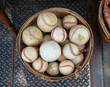 A basket of old weathered baseballs sitting outside on the street