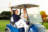 Couple in driving buggy on golf course - 221242950