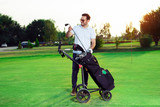 Young man golfer taking out the golf club from a bag - 221242957