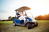 Couple in driving buggy on golf course - 221242970