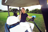 Young woman sitting on golf buggy on green field and having phone call - 221242979