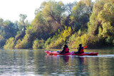 Two girls in a red kayak paddle in autumnal Danube river on a calm autumn day. Landscape with a kayak on a background of yellow autumn trees - 221244704