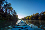 View from the bow of blue kayak on Danube river at sunset. Kayaking on peaceful calm lake or river in clear autumn day - 221244723