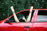 young woman driver resting in a red car, put her feet on the car window and gesturing, happy travel concept - 221245380