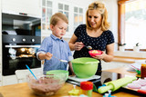 Smart cute child helping mother in kitchen - 221249746