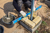The worker lays bricks on the construction site - 221250924