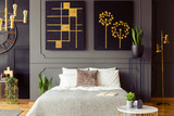 Real photo of a bedroom interior with big, black paintings with golden accents, double bed and plants - 221253341
