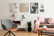 Leinwanddruck Bild - Grey armchair in living room interior with lamp and plant on cabinet next to beige sofa. Real photo