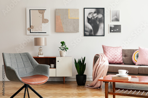 Leinwanddruck Bild Grey armchair in living room interior with lamp and plant on cabinet next to beige sofa. Real photo