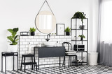 Plant on table in black and white bathroom interior with checkered floor and mirror. Real photo
