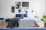 Blanket on bed with blue pillows in white bedroom interior with gallery and lamp on table. Real photo - 221253764