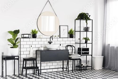 Roślin na stole w czarno-białe wnętrze łazienki z burzliwą podłogą i lustrem. Prawdziwe zdjęcie